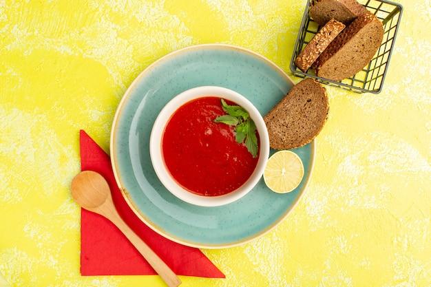 Widok z góry pyszna zupa pomidorowa z bochenkami chleba na żółtym stole, posiłek zupy obiad warzywny