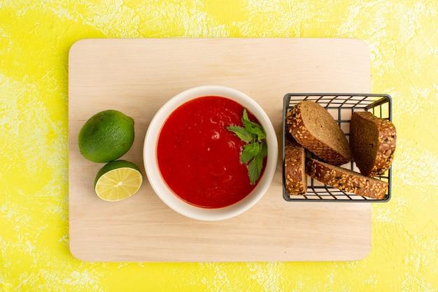 Widok z góry pyszna zupa pomidorowa z bochenkami chleba plasterek cytryny na żółtym stole, posiłek zupy obiad warzywny