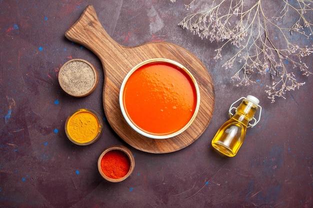 Widok z góry pyszna zupa pomidorowa z przyprawami na ciemnym tle zupa danie pomidorowe sos do posiłku