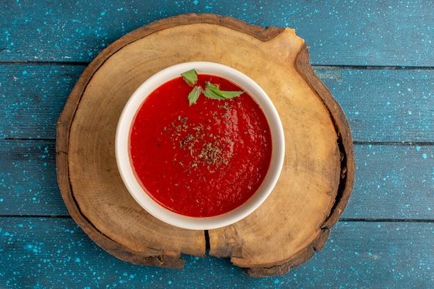 Widok z góry pyszna zupa pomidorowa z przyprawami w środku na niebieskim stole, zupa obiadowa warzywna