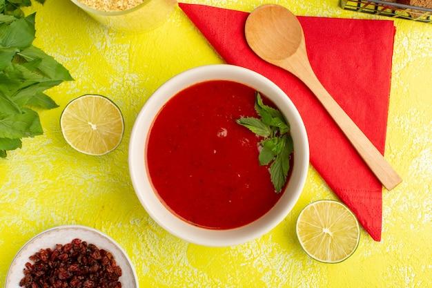 Widok z góry pyszna zupa pomidorowa z zieleniną i cytryną na żółtym stole, posiłek zupy obiad warzywny