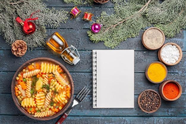Widok z góry pyszna zupa z makaronu ze spiralnego włoskiego makaronu z przyprawami na ciemnoniebieskim biurku kuchnia zupa z makaronu kolacja kolor danie