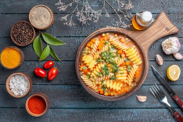 Widok z góry pyszna zupa z makaronu ze spiralnego włoskiego makaronu z przyprawami na ciemnoniebieskim biurku zupa z makaronu kolor danie obiad kuchnia