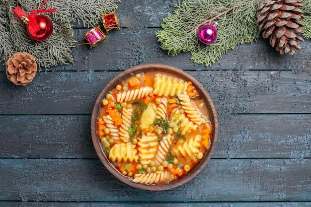Widok z góry pyszna zupa z makaronu ze spiralnego włoskiego makaronu z zielenią na ciemnoniebieskim biurku kuchnia zupa makaronowa kolor danie obiad