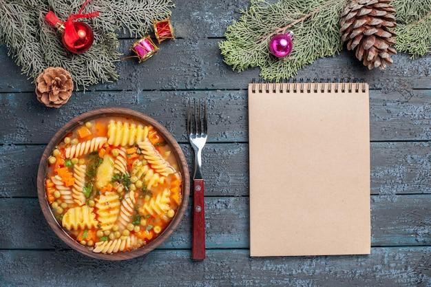 Widok z góry pyszna zupa z makaronu ze spiralnego włoskiego makaronu z zielenią na ciemnoniebieskim tle kuchnia zupa z makaronu kolor danie obiad