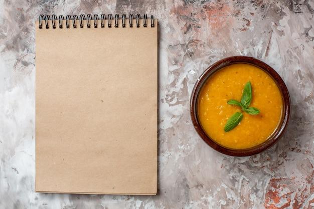 Widok z góry pyszna zupa z soczewicy wewnątrz talerza na jasnym tle zupa roślinna kolorowa nasiona żywności