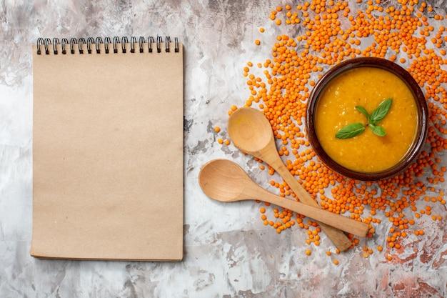 Widok z góry pyszna zupa z soczewicy wewnątrz talerza na jasnym tle zupa roślinna kolorowa potrawa z nasionami