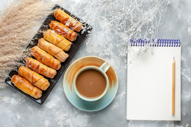 Widok z góry pyszne bransoletki z mleczną kawą i notatnikiem na szarym biurku ciasto ciasto herbatniki słodki cukier