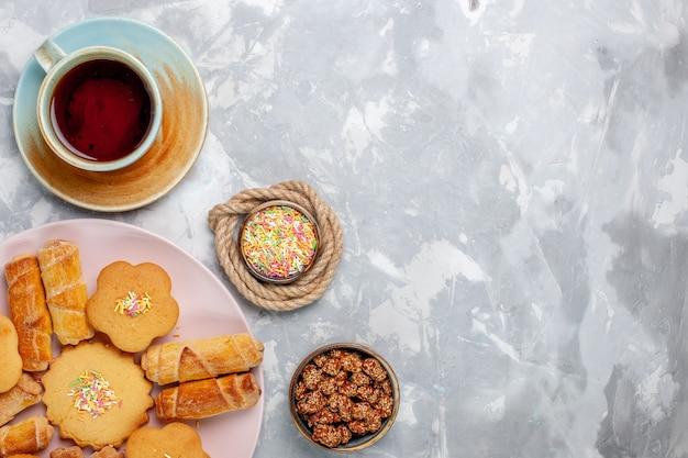 Widok z góry pyszne bułeczki z ciastami i herbatą na białym biurku