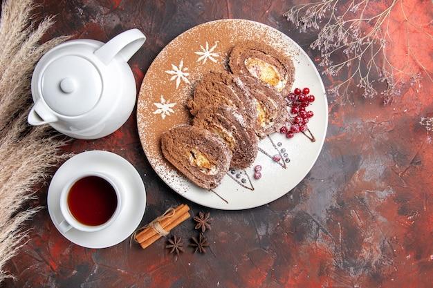 Widok z góry pyszne bułeczki z herbatą na ciemnym stole słodkie ciasto ciasto