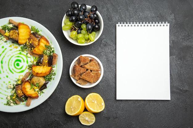 Widok z góry pyszne bułki z bakłażana z pieczonymi ziemniakami wewnątrz talerza na ciemnej podłodze danie posiłek obiad jedzenie ziemniak warzywo
