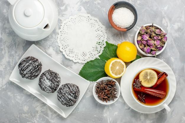 Widok z góry pyszne ciasta czekoladowe mały okrągły utworzony z cytryną na białym biurku owoce ciasto herbatniki słodkie cukier ciasteczka pieczone