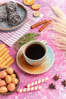 Widok z góry pyszne ciasta czekoladowe z filiżanką herbaty na różowo