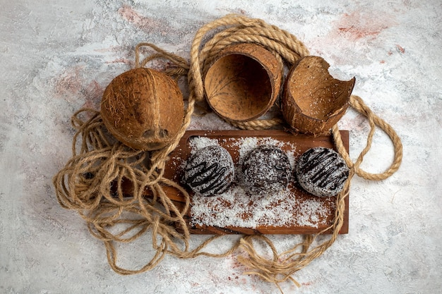Widok z góry pyszne ciasta czekoladowe z kokosem na jasnobiałej powierzchni