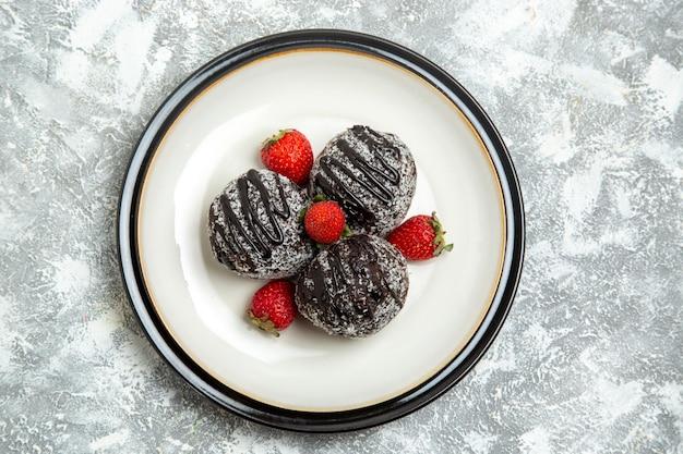 Widok z góry pyszne ciasta czekoladowe ze świeżymi czerwonymi truskawkami na białej powierzchni