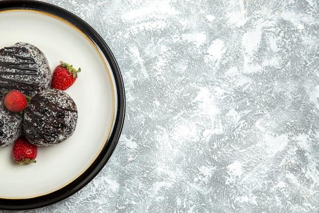 Widok z góry pyszne ciasta czekoladowe ze świeżymi truskawkami na białej powierzchni