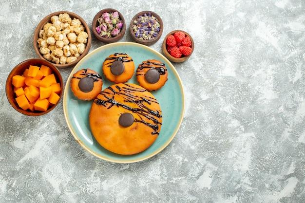 Widok z góry pyszne ciasta kakaowe z polewą czekoladową i kwiatami na białej powierzchni herbatniki słodkie ciasto deserowe ciasto cookie