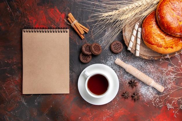 Widok z góry pyszne ciasta na filiżankę herbaty na ciemnej podłodze