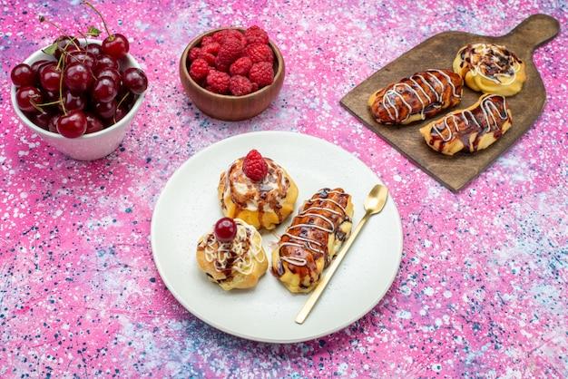 Widok z góry pyszne ciasta owocowe ze śmietaną i czekoladą na białym talerzu wraz ze świeżymi owocami na różowym tle ciasto biszkoptowe słodkie wypieki