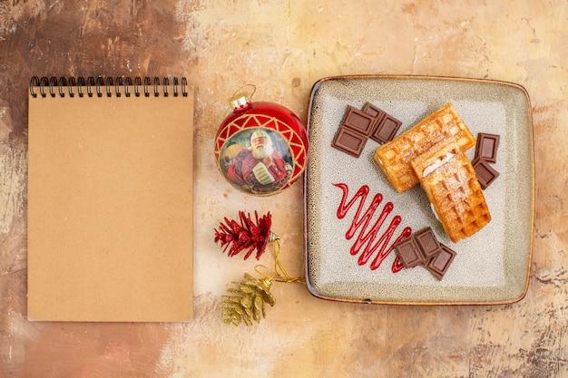 Widok z góry pyszne ciasta waflowe z batonami czekolady na brązowym tle