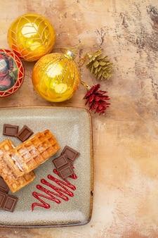 Widok z góry pyszne ciasta waflowe z czekoladą i noworocznymi zabawkami drzewnymi na jasnym tle