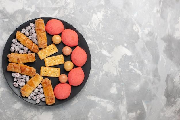 Widok z góry pyszne ciasta z bajglami i cukierkami na jasnej białej powierzchni