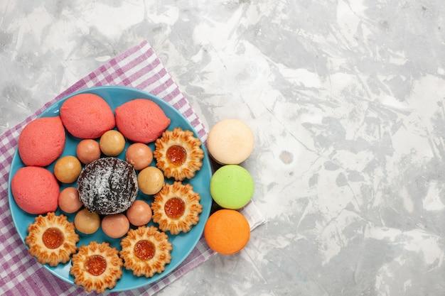 Widok z góry pyszne ciasta z ciasteczkami i makaronikami na białej powierzchni
