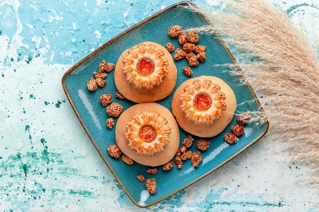 Widok z góry pyszne ciasta z ciasteczkami i słodkimi orzechami na jasnoniebieskiej powierzchni upiec ciasto biszkoptowe słodki cukier orzechowy