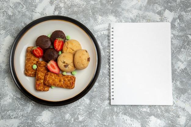 Widok z góry pyszne ciasta z ciasteczkami i truskawkami na jasnobiałym tle biszkoptowe ciasto cukrowe słodkie ciastko herbaty