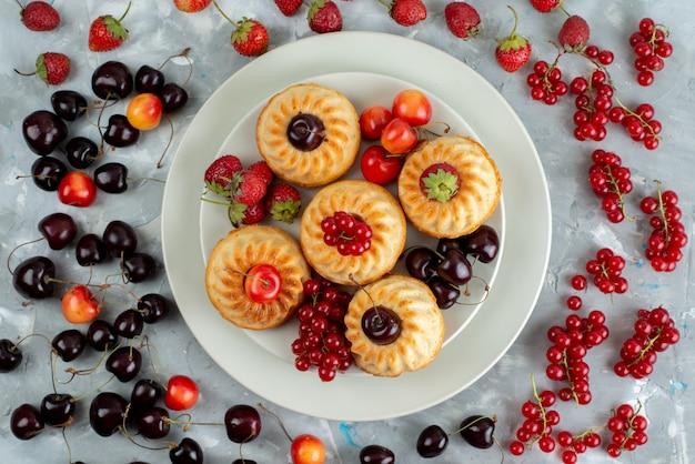 Widok z góry pyszne ciasta z łagodnymi i soczystymi czerwonymi owocami wewnątrz białego talerza na lekkim biurku jagodowym