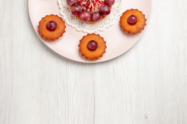 Widok z góry pyszne ciasta z winogronami wewnątrz płyty na białym stole, ciasto deserowe
