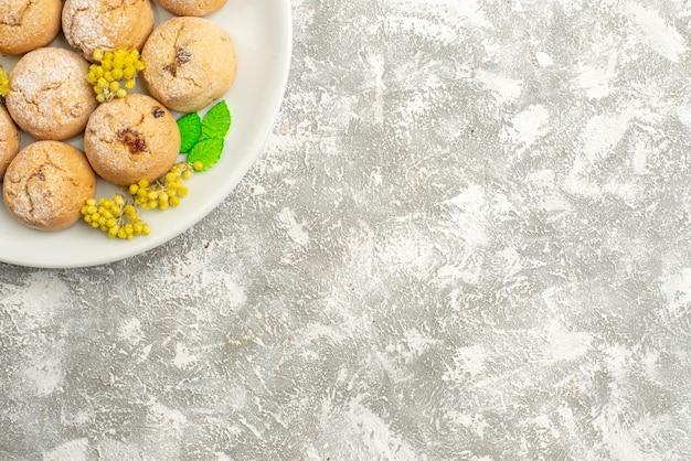 Widok z góry pyszne ciasteczka cukrowe wewnątrz płytki na białym tle ciasteczka cukru słodkie herbatniki herbatniki