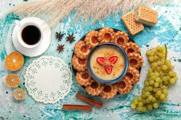 Widok z góry pyszne ciasteczka cukrowe z goframi filiżanka kawy i deser truskawkowy na niebieskim biurku