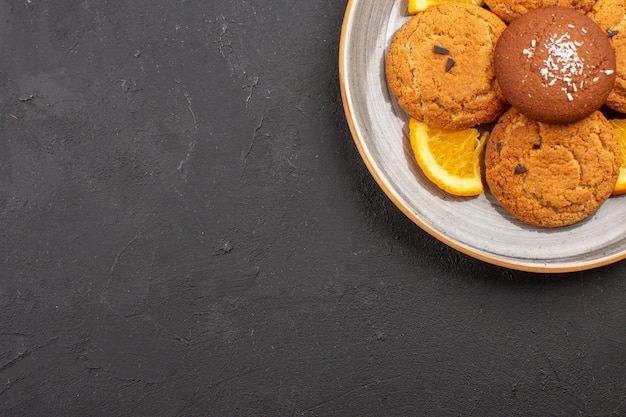 Widok z góry pyszne ciasteczka cukrowe z pokrojonymi pomarańczami wewnątrz talerza na ciemnym tle herbatniki cukrowe słodkie ciasteczka owocowe
