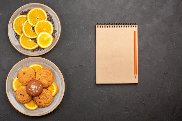 Widok z góry pyszne ciasteczka cukrowe ze świeżymi pokrojonymi pomarańczami na ciemnej podłodze herbatniki cukrowe słodkie ciasteczka owocowe