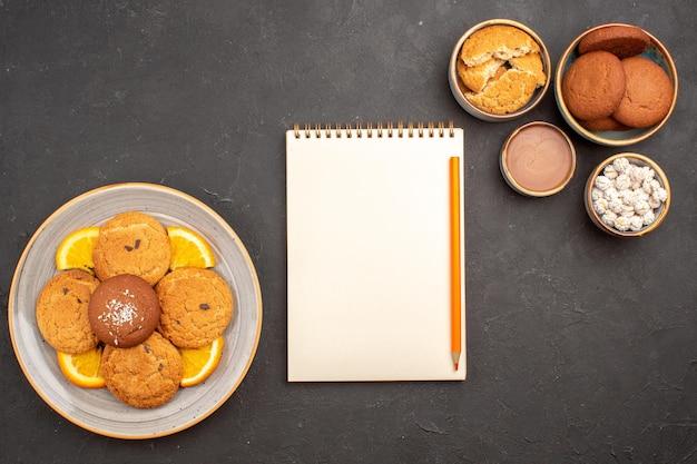 Widok z góry pyszne ciasteczka cukrowe ze świeżymi pokrojonymi pomarańczami na ciemnym tle ciastko z cukrem owocowym słodkie