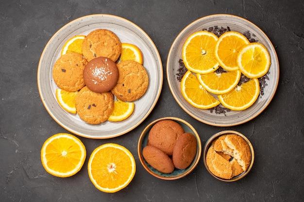 Widok z góry pyszne ciasteczka cukrowe ze świeżymi pokrojonymi pomarańczami na ciemnym tle herbatniki cukrowe słodkie ciasteczka owocowe