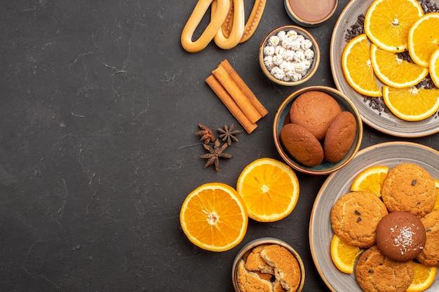 Widok z góry pyszne ciasteczka piaskowe ze świeżymi pomarańczami na ciemnym tle ciastko cukier owocowy herbatnik słodki cytrusowy