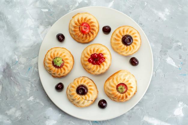 Widok z góry pyszne ciasteczka wewnątrz białej tablicy z wiśniami i truskawkami na lekkim biurku ciasto owocowe