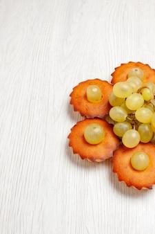 Widok z góry pyszne ciasteczka wyłożone winogronami na białym biurku ciasto herbaciane ciasto słodkie ciasteczka deserowe