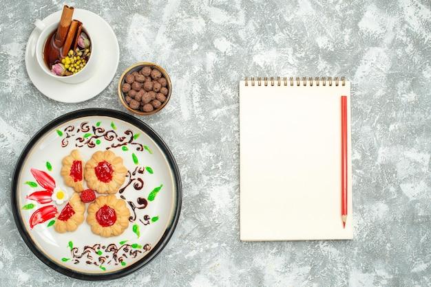 Widok z góry pyszne ciasteczka z czerwoną galaretką i filiżanką herbaty na białym tle cukrowe ciastko biszkoptowe ciastko słodka herbata