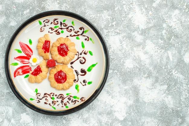 Widok z góry pyszne ciasteczka z czerwoną galaretką wewnątrz talerza na białym tle ciasteczka słodkiej herbaty
