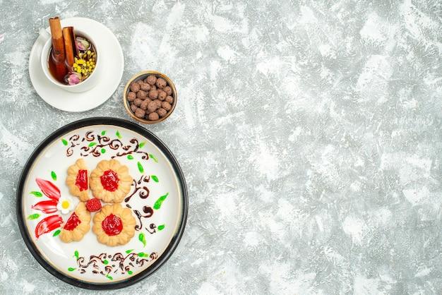 Widok z góry pyszne ciasteczka z czerwoną galaretką wewnątrz talerza na białym tle cukrowe ciasteczka biszkoptowe słodka herbata