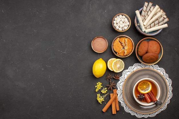 Widok z góry pyszne ciasteczka z filiżanką herbaty na ciemnej powierzchni ciasteczko słodkie herbatniki cytrusowe cukier owocowy