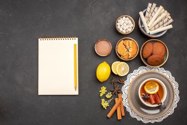 Widok z góry pyszne ciasteczka z filiżanką herbaty na ciemnym ciasteczku na biurku słodkie herbatniki cytrusowe cukier owocowy
