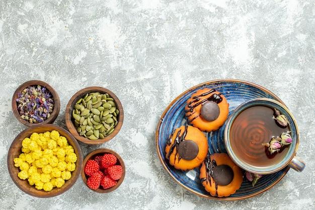 Widok z góry pyszne ciasteczka z filiżanką herbaty na jasnej białej powierzchni ciasto herbatniki ciastko deser herbata słodka