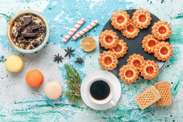 Widok z góry pyszne ciasteczka z filiżanką kawy macarons i gofry na niebieskim biurku herbatniki herbatniki słodki cukier kolor herbaty