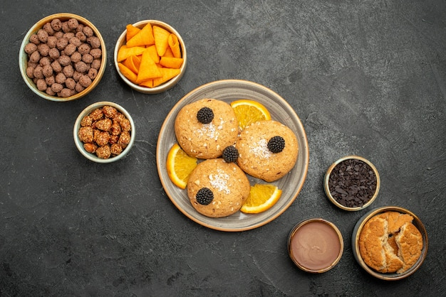 Widok z góry pyszne ciasteczka z frytkami i orzechami na ciemnoszarej powierzchni ciasteczko herbatniki herbata słodkie ciasto