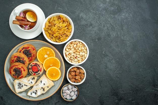 Widok z góry pyszne ciasteczka z owocowymi wypiekami pomarańczowa herbata i orzechy na ciemnej powierzchni orzechowa przekąska herbata słodki cukierek
