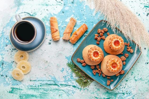 Widok z góry pyszne ciasteczka z suszonymi krążkami ananasa bułeczki i kawa na niebieskiej powierzchni ciasteczka biszkoptowe w kolorze słodkiego cukru